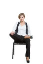 Woman sits astride a chair. legs crossed, fixed Royalty Free Stock Photo