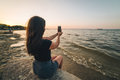 Woman sits on a beach and takes picture of the seaside Royalty Free Stock Photo