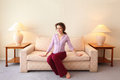 Woman sits on couch in simple room Royalty Free Stock Photography