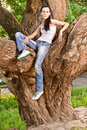 Woman sits on huge tree i Royalty Free Stock Photos