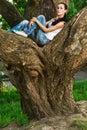 Woman sits on huge tree i Stock Photos
