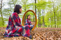 Woman sits with mirror in forest during spring Royalty Free Stock Photo