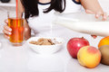 Woman sits at a table and eat breakfast. Women eating healthy food for breakfast. Fruit, cereal and milk, close up selective focus