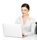 Woman sits from the table with laptop in white shirt beautiful smiling thу isolated on Stock Image