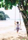 Woman sits on the tree swing on the Weligama sandy beach coast