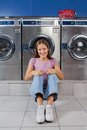 Woman sitting against washing machines at laundry portrait of beautiful young on floor Stock Image