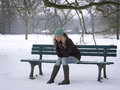 Woman sitting alone on park bench in winter snow covered with depression Royalty Free Stock Photos