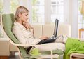 Woman sitting in armchair with feet up working with computer at home in living room Stock Photo