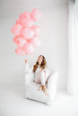 Woman sitting in an armchair and holding a bunch of pink balloons