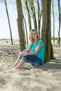 Woman sitting on beach beautiful blonde the sand of a with her back against a tree with her arms wrapped around her knees Stock Photo