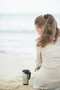 Woman sitting on beach with cup of hot beverage cold Stock Images