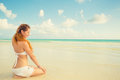 Woman sitting on a beach enjoying sunny day tropical weather Royalty Free Stock Photo