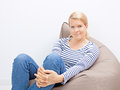 Woman sitting on a beanbag beautiful blond Royalty Free Stock Images