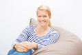 Woman sitting on a beanbag beautiful blond Stock Photography