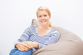 Woman sitting on a beanbag beautiful blond Stock Images