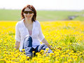 Woman is sitting in a beautiful meadow Royalty Free Stock Image