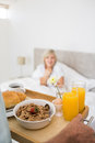 Woman sitting in bed with breakfast in foreground happy mature at home Stock Photo