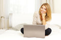 Woman sitting on the bed with laptop young beautiful at home Stock Photography