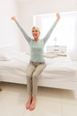 Woman sitting bed stretching smiling middle aged on and Stock Photography
