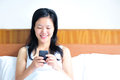 Woman sitting on the bed using her smartphone a smiling leans Royalty Free Stock Photo