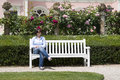 Woman sitting at bench a a garden Royalty Free Stock Images