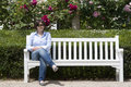 Woman sitting at bench a a garden Stock Photos
