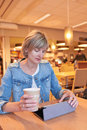 Woman sitting in the cafe with cup of coffee and digital tablet Stock Photo