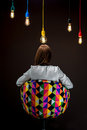 Woman sitting on the chair with illuminated colorful lamps Royalty Free Stock Photo