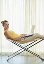 Woman sitting on chair and working on laptop Royalty Free Stock Photo