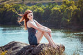 Woman sitting on the cliff beautiful young above river with her eyes closed enjoying warm breeze waving her red long hair Royalty Free Stock Images