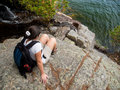 Woman sitting on a cliff over lake in acadia national park Royalty Free Stock Photo