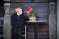 Woman sitting close old cottage middle aged black near flower on the table Stock Image