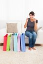 Woman sitting on couch excited young with multiple shopping Royalty Free Stock Photos