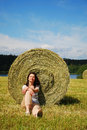 Woman sitting down the stubble-field Stock Photography