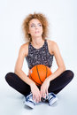 Woman sitting on the floor with basketball ball Royalty Free Stock Photo