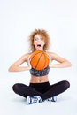 Woman sitting on the floor with basketball ball and screaming Royalty Free Stock Photo