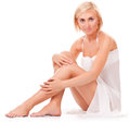 Woman sitting on the floor showing her slim legs young in white is engaged in body care Royalty Free Stock Images