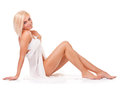 Woman sitting on the floor showing her slim legs young in white is engaged in body care Royalty Free Stock Photos
