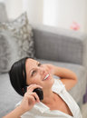 Woman sitting on floor and speaking cell phone Stock Images