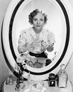 Woman sitting in front of her vanity looking into the mirror Royalty Free Stock Photo