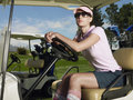 Woman sitting in golf cart beautiful female golfer wearing sunglasses Royalty Free Stock Photography