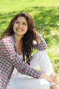 A woman sitting on the grass in plaid shirt green Stock Image