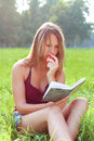 Woman sitting in grass reading book Royalty Free Stock Photo