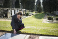 Woman sitting at grave on graveyard of deceased relative sad mourning Royalty Free Stock Photo