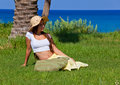 Woman is sitting on green grass near the sea Stock Images