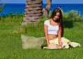 Woman is sitting on green grass near the sea Royalty Free Stock Photography