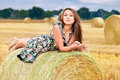 Woman  sitting on hay bale Stock Photos