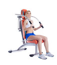 Woman sitting on hydraulic exerciser isolated Stock Images