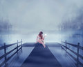 Woman sitting on a lake pier with bright ball of glowing light in her hand Royalty Free Stock Photo