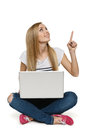 Woman sitting with laptop on the floor pointing up, Royalty Free Stock Photo